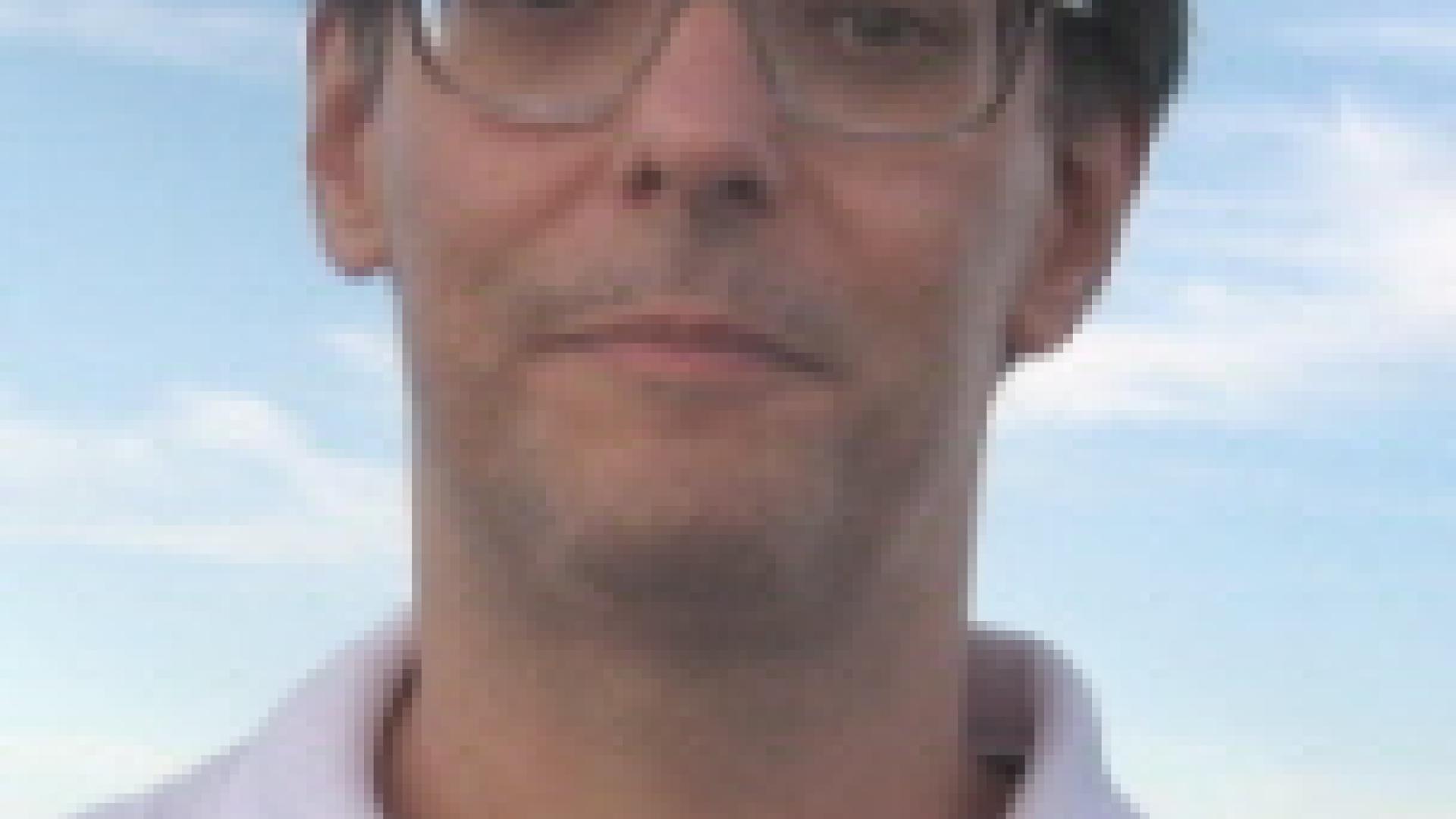 foto do professor Fábio, com fundo azul, homem branco, cabelos castanhos curtos e óculos