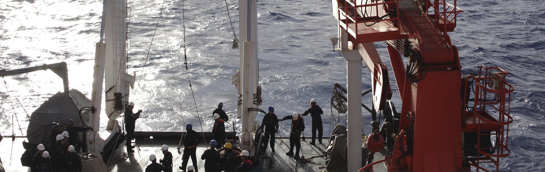 Imagem: Pessoas trabalhando a bordo do Navio de Pesquisa Hidroceanográfico Vital de Oliveira com mar ao fundo