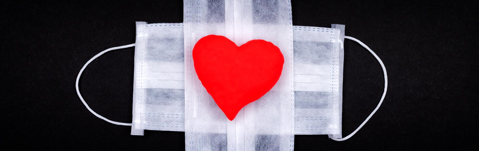 imagem de duas máscaras brancas de proteção facial com um coração estampado em uma delas