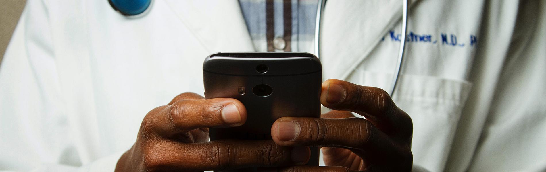close nas mãos de um médico de jaleco usando um smartphone