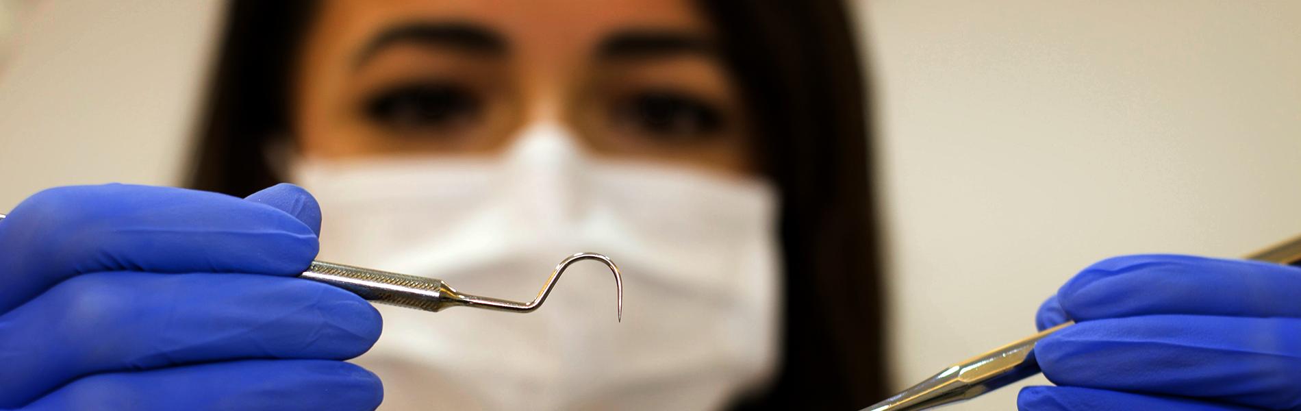 close de uma dentista com máscara e luvas segurando aparatos odontológicos