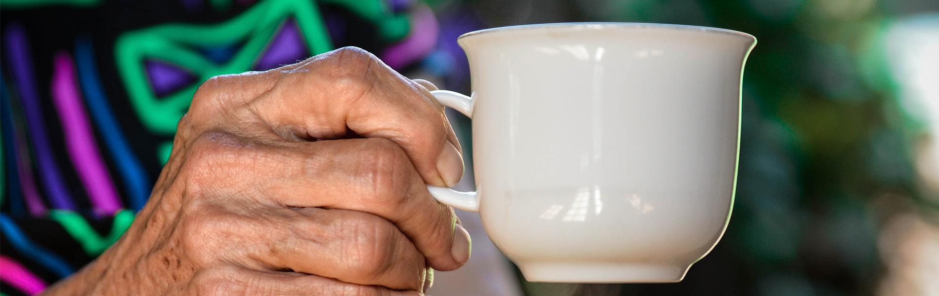 Foto em close up de idoso ou idosa segurando xícara de porcelana