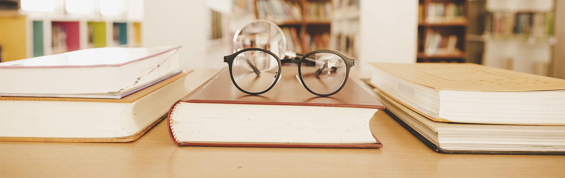 Banner com fundo bege com uma mesa, livros e óculos