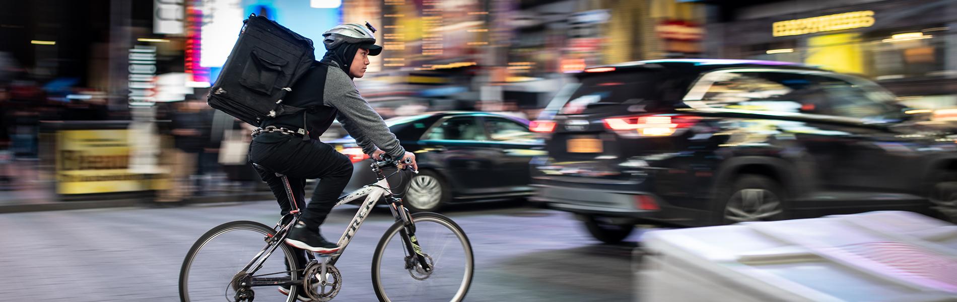 Homem de bicicleta com mochila de serviço de delivery. Ao fundo, carros e prédios desfocados.