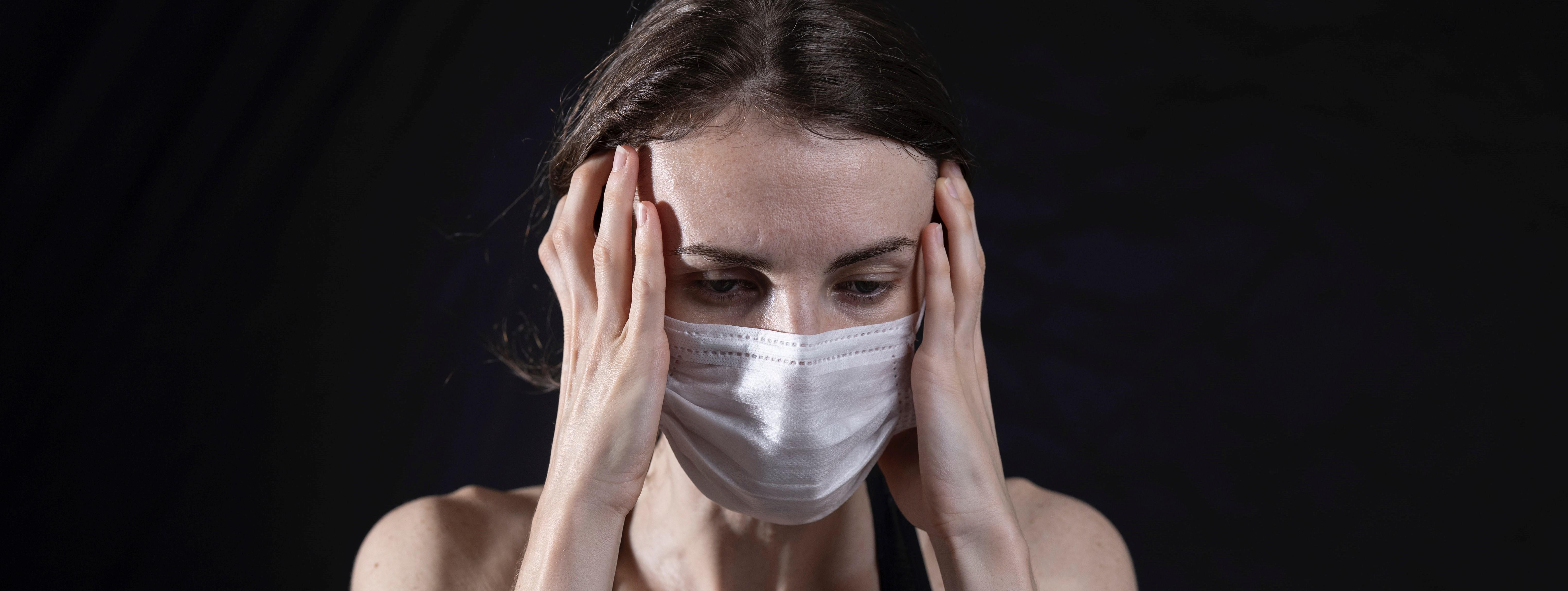 mulher de máscara com as mãos na cabeça e expressão triste