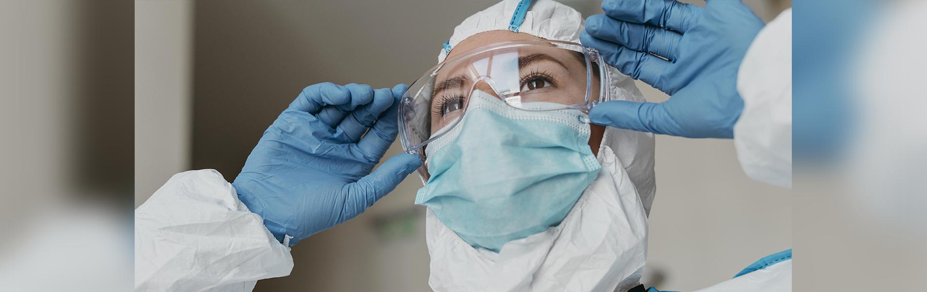 Médica de luvas colocando óculos de proteção