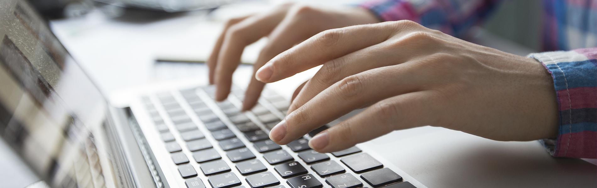 Mãos de mulher digitando em um computador
