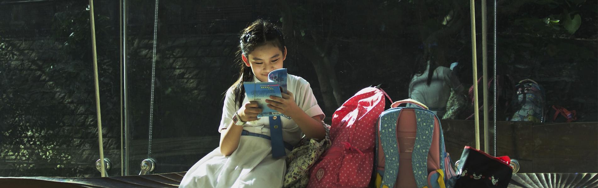 Imagem: Criança oriental lendo sentada em um banco