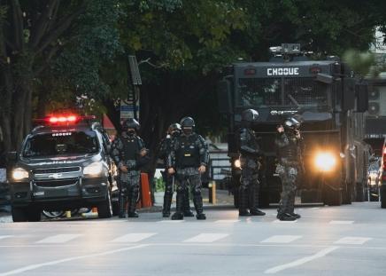 Carro da polícia de choque, policiais e camburão de choque parados em uma avenida