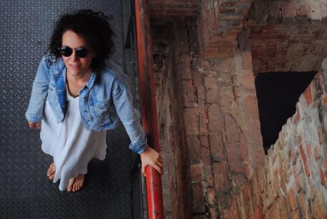 """Foto tirada """"de cima"""", em que aparece uma mulher com óculos escuros segurando um corrimão vermelho e olhando para cima"""