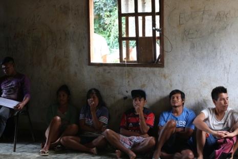 Indígenas sentados lado a lado, em um espaço fechado, abaixo de uma janela aberta