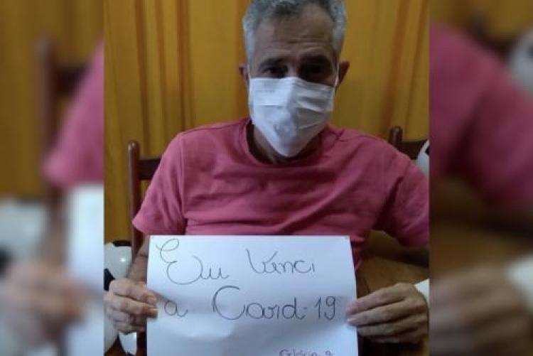 homem de camisa rosa, de máscara branca, sentado em cadeira de rodas, segurando um papel com os dizeres: eu venci a Covid-19