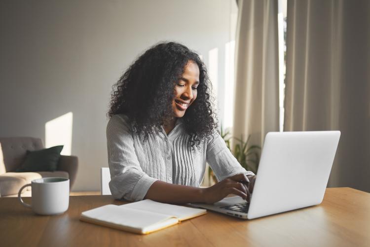 Mulher sorrindo e digitando em laptop