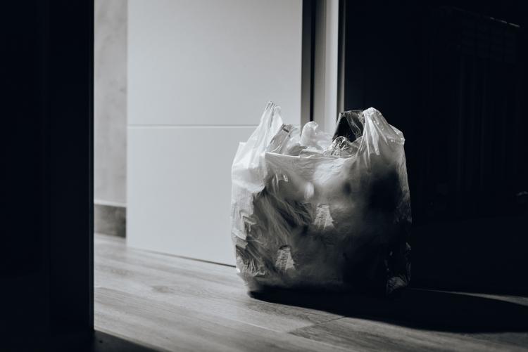 Foto de sacola de plástico cheia de lixo ao lado de uma porta aberta