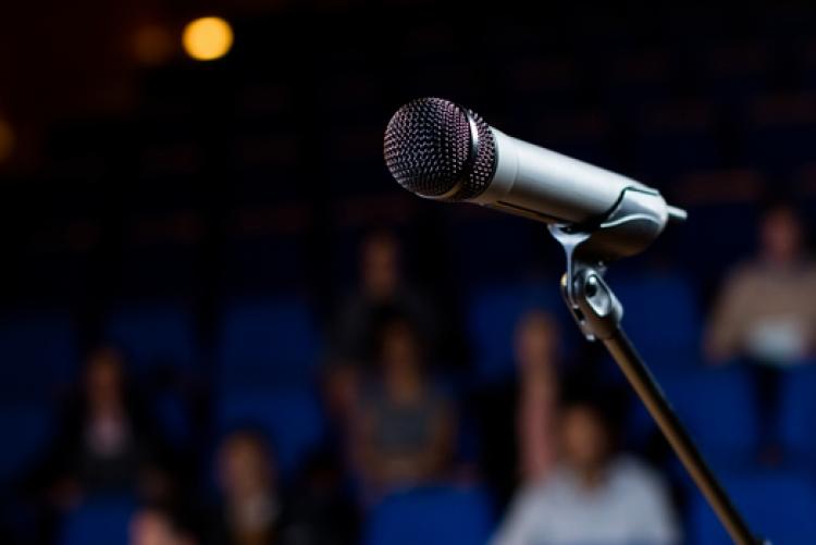 Imagem de microfone em pedestal com público ao fundo desfocado.