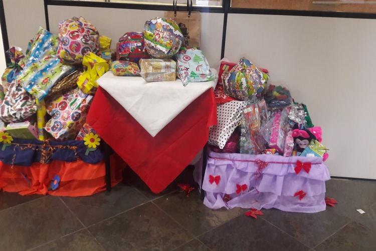 Caixas decoradas contendo embrulhos com presentes para crianças.