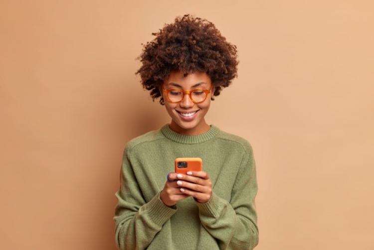 Mulher negra sorrindo e observando tela de celular