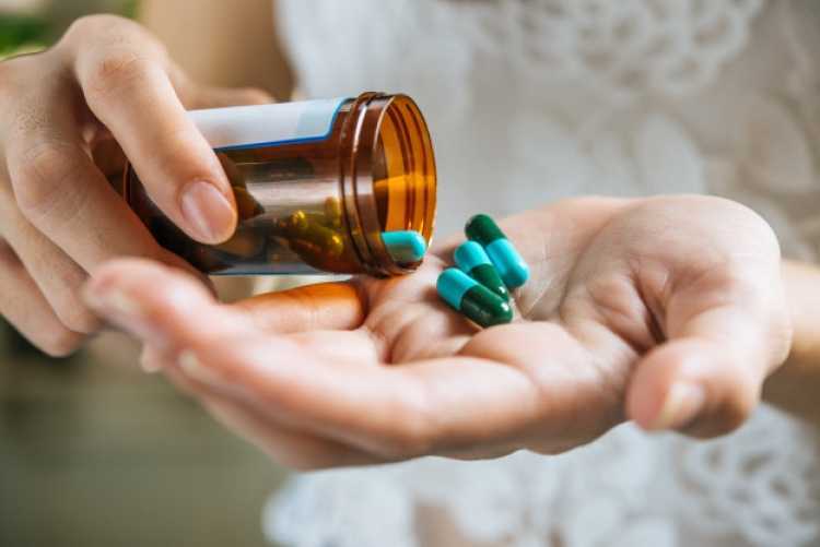 Close up de uma mão derramando pílulas de um vidrinho na outra mão