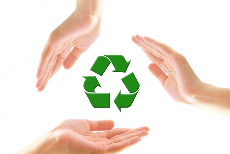 Mãos de pessoas envolvendo o símbolo da reciclagem