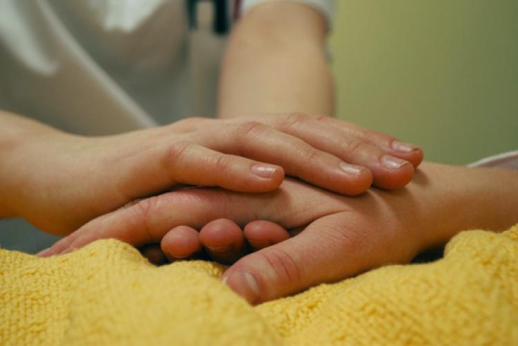 close nas mãos de duas pessoas. Uma está confortando a outra.