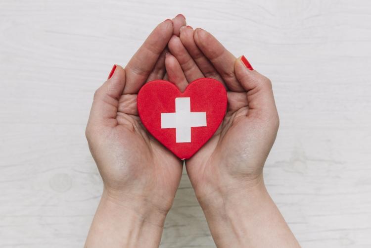 imagem: par de mãos segurando um coração vermelho com o desenho de uma cruz branca