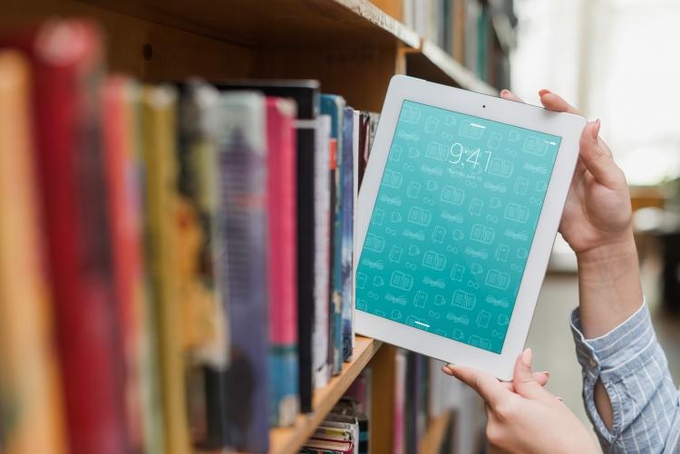 Foto de pessoa retirando um Ipad de estante de livros