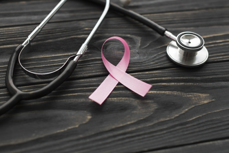 Imagem: estetoscópio e fita rosa em cima de uma mesa