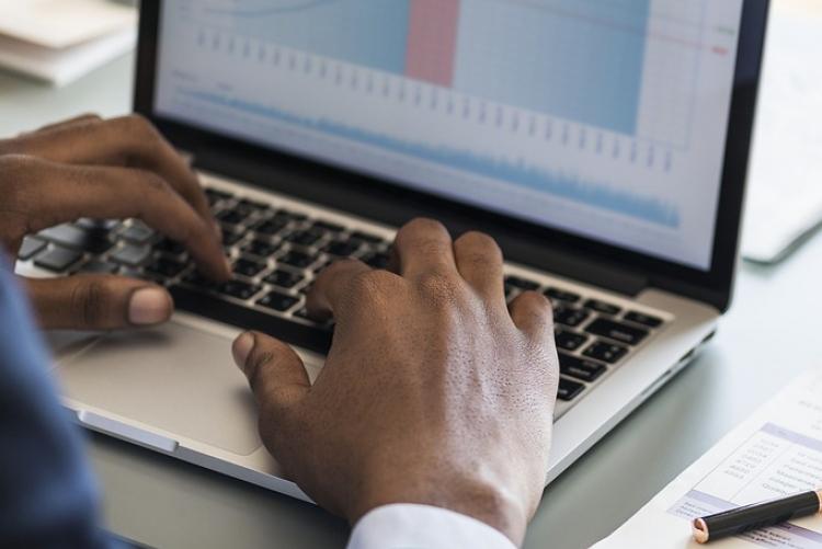 Mãos digitando em um laptop