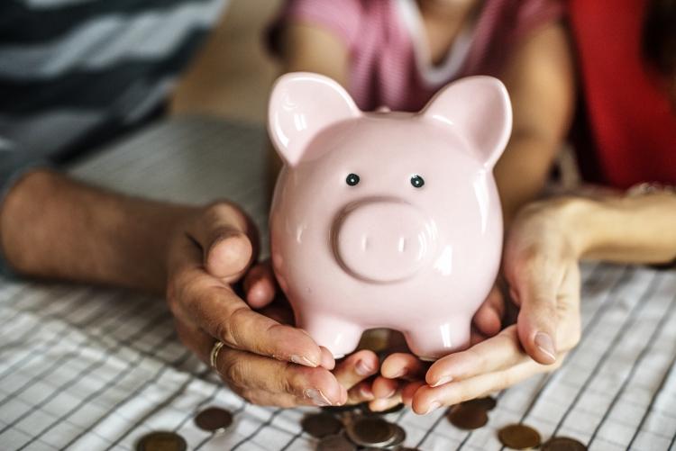 Quatro mãos segurando um cofre em forma de porquinho em cima de uma mesa com moedas espalhadas