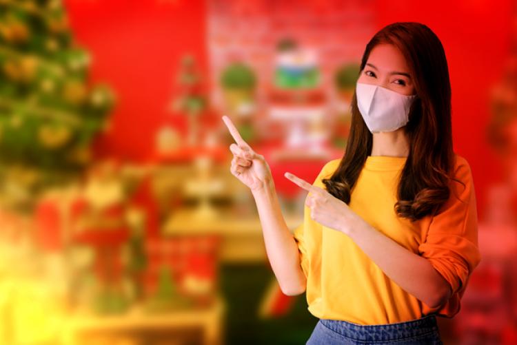 Mulher branca de blusa amarela e calça azul usando máscara com dois dedos indicadores apontando para o lado. Ao fundo parede vermelha e árvore natalina desfocada.
