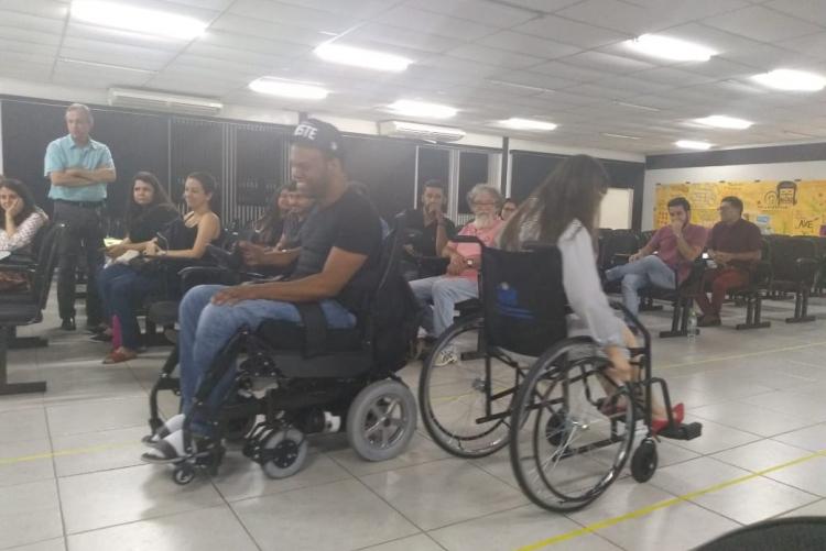 #pratodosverem imagem que registra o momento de uma dinâmica realizada no auditório. Ao centro, um homem e uma mulher, de costas um para o outro, ambos em cadeiras de rodas. À direita, pessoas na plateia observam a atividade. Fim da descrição.