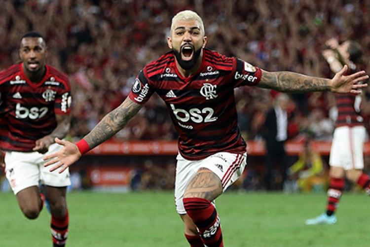 foto de jogador de futebol com camisa vermelha e preta, braços e bocas abertos, comemorando