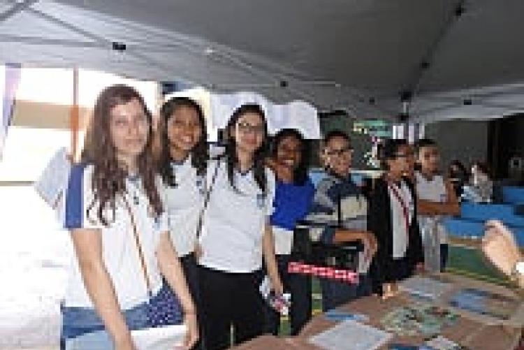 Alunos tirando dúvidas no estande da UFF com a  Bibliotecária Zilma de Jesus e os alunos do Curo