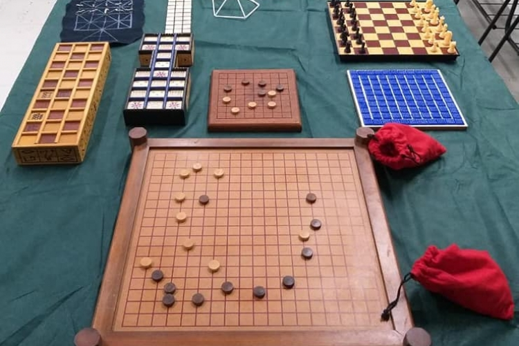 #pratodosverem mesa com fundo verde escuro onde estão expostos vários modelos de jogos em forma de tabuleiros, caixas coloridas e formas geométricas. Fim da descrição.