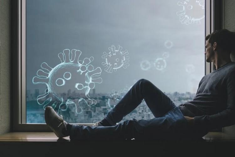 Homem recostado em um parapeito de janela olha para a paisagem da cidade do lado de fora. Ilustrações da estrutura do coronavírus entram por sua janela.