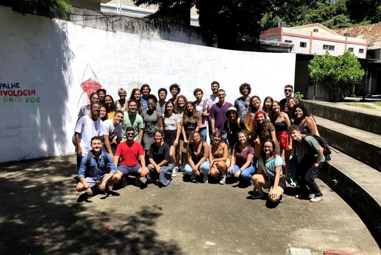 Muitos alunos de cinema reunidos em um pátio, cercado por escadas, num dia de sol