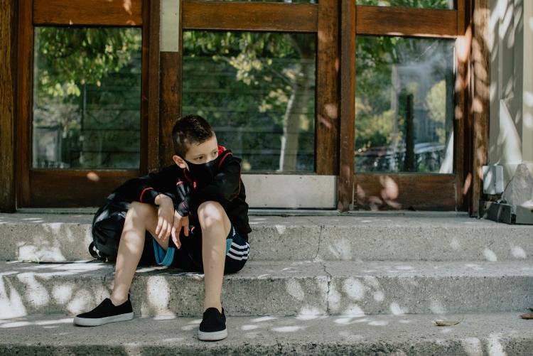 Criança de máscara sentada em um degrau, em frente a uma porta de vidro fechada.