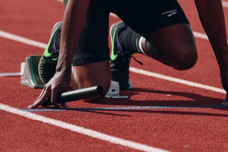Atleta iniciando corrida em pista de atletismo