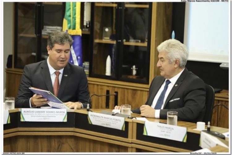 À esquerda o professor Aurélio Lamare segurando um papel e apresentando ao Ministro Marcos Pontes, que está à direita.