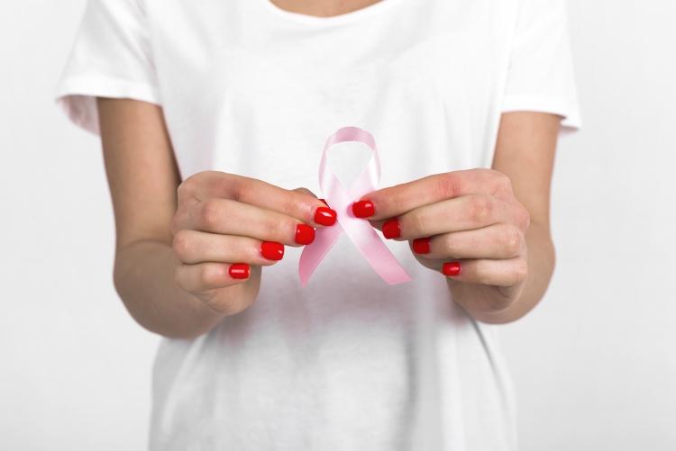 imagem: mãos segurando uma fita rosa, que é o símbolo da campanha outubro rosa