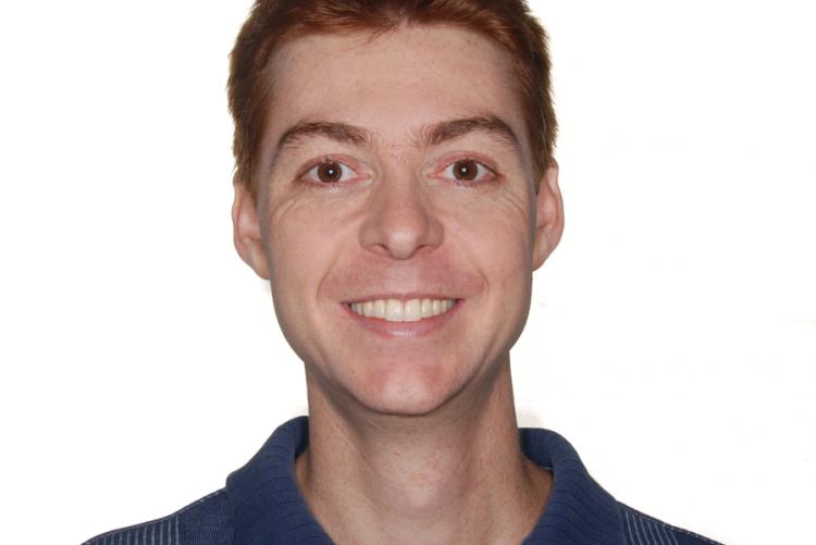Foto de homem branco, cabelo ruivo, blusa azul