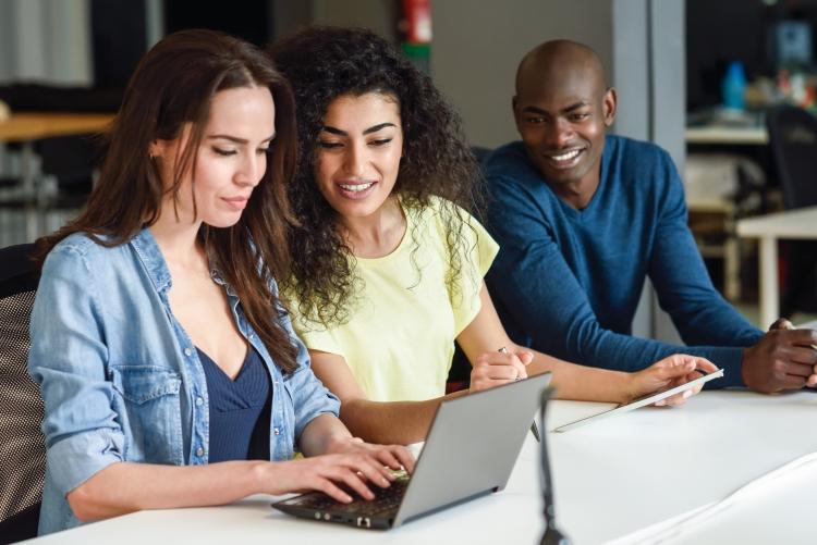 imagem: uma mulher digitando no notebook e duas pessoas ao lado olhando