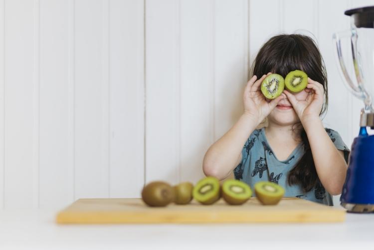 imagem: criança segurando duas metades de kiwi