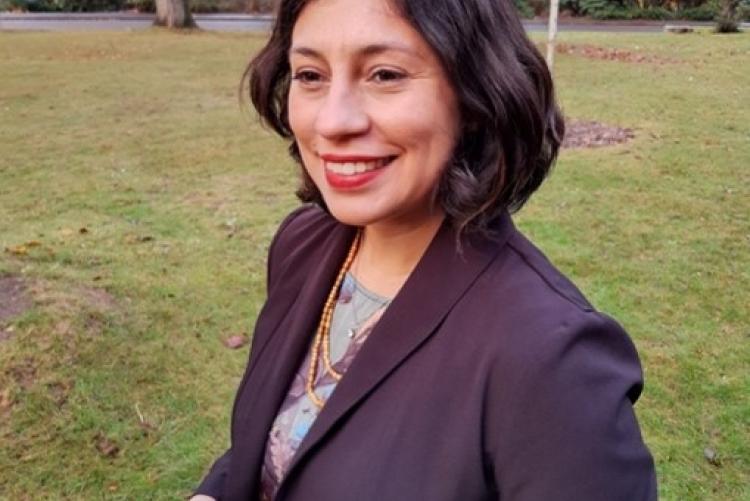 Foto da pesquisadora de pele clara, cabelos curtos e pretos, fundo gramado