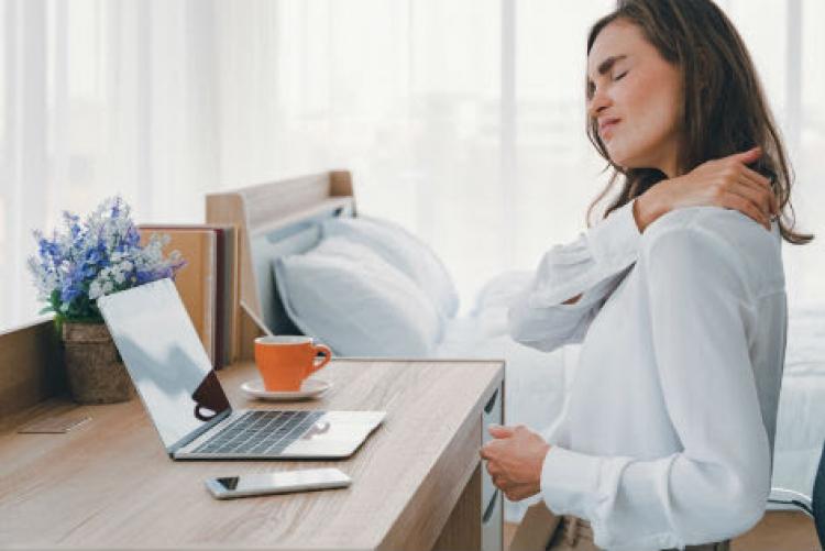 Mulher sentada em escrivaninha de frente para um laptop com a mão direita massageando o ombro esquerdo e expressão facial de desconforto