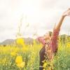 Imagem: mulher em um campo florido de braços abertos