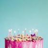 Imagem de bolo de aniversário colorido com velas em um fundo azul turquesa