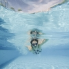 Imagem: mulher com óculos de mergulho nadando em uma piscina azul