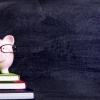 imagem: porquinho de louça em cima de três livros empilhados com quadro-negro de fundo
