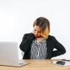 imagem: mulher em frente ao computador com mãos sobre a nuca e testa franzida